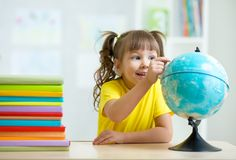 Kid girl pointing at globe. And sitting at table with books Stock Image