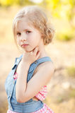 Kid girl posing on nature background. Portrait of cute kid girl looking at camera Stock Photos