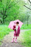 Kid girl posing outdoors with pink umbrella Stock Images