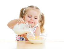 Kid girl eating corn flakes with milk. Kid girl preparing corn flakes with milk stock photos