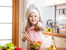 Kid girl preparing food and showing thumb up Stock Photography