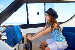 Kid girl pretending be a captain sailor cap in boat Stock Images