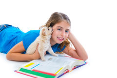 Kid girl with puppy chihuahua pet dog at homework. Kid girl with puppy chihuahua pet dog doing homework lying on white background stock photography