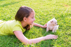 Kid girl and puppy dog happy lying in lawn Royalty Free Stock Photography