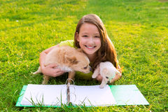 Kid girl and puppy dog at homework lying in lawn Royalty Free Stock Image