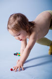 Kid girl reaching small ball. Funny baby girl catching rolling small ball stock images