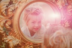 Kid girl reflect in mirror on sunny day. Kid girl with adorable face, blond hair reflect in mirror on sunny day. Child beauty, look concept royalty free stock photos