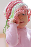 Kid girl removing her hat. Pretty kid girl attemting to remove her pink hat stock image