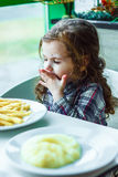 Kid girl in a restaurant eating fast food. Royalty Free Stock Images