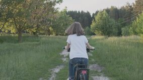 Kid girl rides a bike, girls first cycling success, sunset country road, natural landscape background, back view