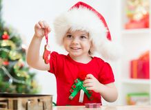 Kid girl in Santa hat holding Christmas biscuits Stock Photography
