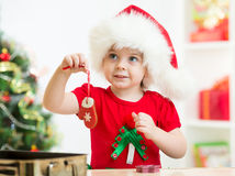 Kid girl in Santa hat holding Christmas cookies. Cute kid girl in Santa hat holding Christmas cookies Royalty Free Stock Images