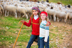 Kid girl shepherdess sisters happy with flock of sheep and stick Royalty Free Stock Photo