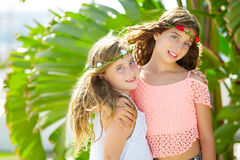 Kid girl sisters hug banana tree leaves bright day Stock Photo