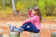 Kid girl sitting in forest trunk looking far away. With hand in forehead royalty free stock photography
