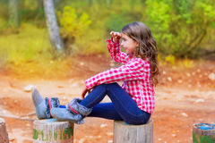 Kid girl sitting in forest trunk looking far away. With hand in forehead stock images