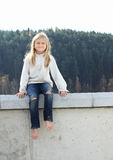 Kid - girl sitting on railing Stock Image