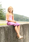 Kid - girl sitting on railing Royalty Free Stock Images