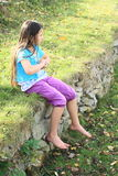 Kid - girl sitting on stone wall. Barefoot girl with long brunette hair in blue t-shirt and lila shorts sitting on stone wall with grass Royalty Free Stock Photography