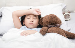 Kid girl sleeping and sick on the bed with bear doll. Kid girl sleeping and sick on the bed with teddy bear doll, healthy concept stock photos
