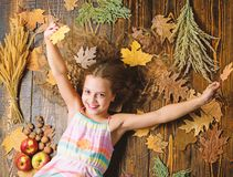 Kid girl smiling face relax wooden background autumn attributes top view. Child with long hair with autumn maple leaves. Tips for turning autumn into best stock photo