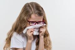 Kid girl sneezes in handkerchief. Flu season, white backgroud, copy space. Kid girl sneezes in handkerchief. Flu season, white backgroud, copy space Royalty Free Stock Images