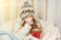Kid girl sneezes in handkerchief at home, The season is autumn winter. Kid girl sneezes in a handkerchief at home, The season is autumn winter Royalty Free Stock Photos