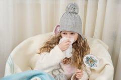 Kid girl sneezes in handkerchief at home, The season is autumn winter. Kid girl sneezes in a handkerchief at home, The season is autumn winter Stock Image