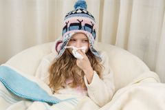 Kid girl sneezes in handkerchief at home, The season is autumn winter. Kid girl sneezes in a handkerchief at home, The season is autumn winter Stock Photos
