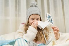 Kid sneezes in a handkerchief at home, The season is autumn winter. Kid girl sneezes in a handkerchief at home, The season is autumn winter Stock Photography