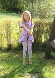 Kid - girl on swing. Barefoot kid - smiling girl in lila clothes sitting and swinging on a rope swing Royalty Free Stock Photos