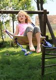 Kid - girl on swing. Barefoot kid - smiling girl in pink and grey clothes sitting and swinging on a swing royalty free stock photo