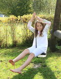 Kid - girl on swing. Barefoot kid - girl in white clothes sitting and swinging on a rope swing royalty free stock image
