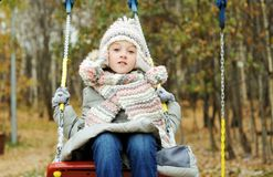 Kid girl on a swing at beautiful winter day Stock Image