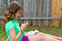 Kid girl taking photos to puppy dog with camera. Kid girl taking photos to puppy dog pet with camera in outdoor backyard stock photos