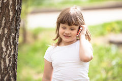 Kid girl talking on the phone outdoor,  spring greens Royalty Free Stock Photo