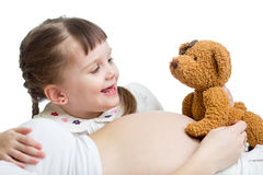 Kid girl telling a tale to baby in pregnant mother's belly Royalty Free Stock Images