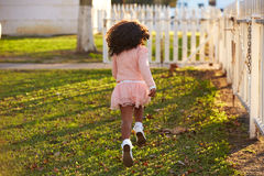 Kid girl toddler playing running in park rear view royalty free stock images