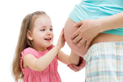 Kid girl touching pregnant mother's belly  Royalty Free Stock Photo