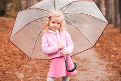 Kid girl with umbrella in park. Stylish kid girl 3-4 year old holding umbrella and wearing autumn clothes in park. Looking at camera. Autumn season royalty free stock photos