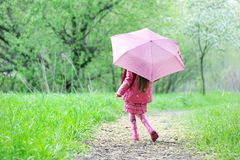 Kid girl walking outdoors with pink umbrella Royalty Free Stock Images