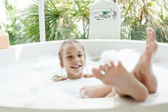 Kid girl washing in bath. Kid girl washing with a foam in luxury hotel outdoor bath, still life Stock Image