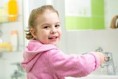 Kid girl washing hands in bathroom Royalty Free Stock Photography