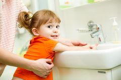 Kid girl washing hands with mom help Royalty Free Stock Photography