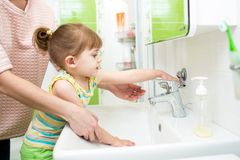 Kid girl washing hands with soap in bathroom Stock Photo
