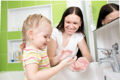 Kid girl washing hands with soap in bathroom. Kid girl washing hands with mom help in bathroom stock image