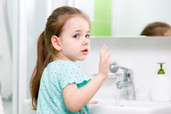Kid girl washing her face and hands in bathroom Royalty Free Stock Photo