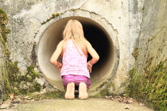 Kid - girl watching into sluice-way Royalty Free Stock Photos