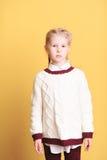 Kid girl wearing sweater in studio. Portrait og cute kid girl posing in studio on yellow background Royalty Free Stock Images