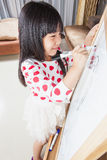 Kid girl writes on a white board with black mark pen. Stock Photo